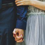 deux mariés se tiennent l'un a cote de l'autre, mains dans la main - mariage