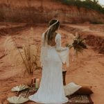 une jeune mariée se tient debout de dos avec un bouquet de fleurs sechées à la mai, elle porte une robe blanche fluide et est dans une ambiance boho, bohemienne pour son mariage