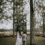 deux mariés marchent de dos pour rejoindre leur invités à leur cérémonie pour un mariage laïc dans la fôret
