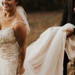 zoom sur un marié qui porte la traine de sa femme qui porte une belle robe blanche pour leur mariage - la mariée semble heureuse